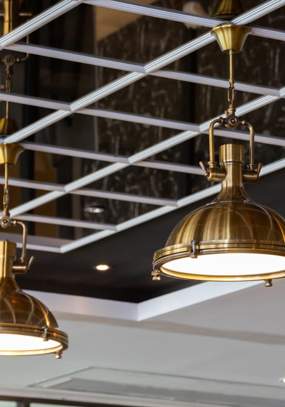 brass hanging lamps on mirror ceiling. golden pendant light decorate in dining room. metal lantern for interior light.